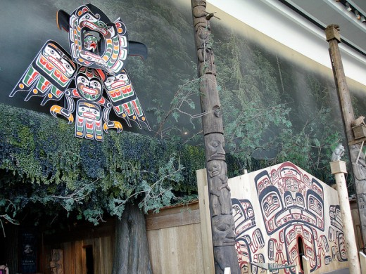 Tsimshian art on an indigenous house, with related native-carved poles.