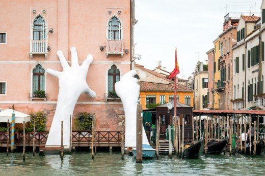 Support, an art installation by Lorenzo Quinn. Giant hands reach out of the Grand Canal. They depict the need to prop up crumbling buildings such as the Palazzo Sagredo.