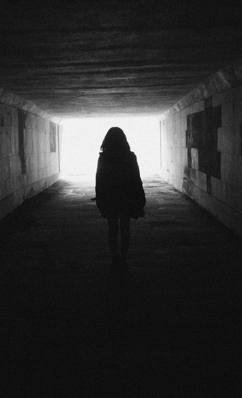 Depiction of woman walking down a dark hallway in to light