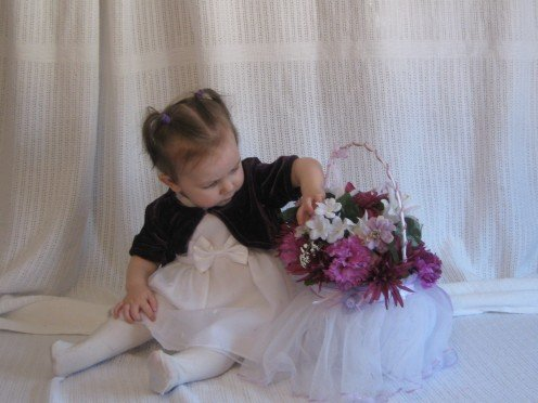This is my youngest daughter, Kayleigh playing with the flower girl basket that I made for the wedding.  The basket was purchased at Wal-Mart and I added the flowers.