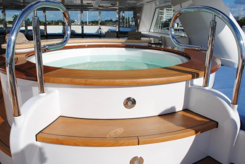 This type of Jacuzzi hot tub is most likely going to be found on a very nice luxury cruise liner when a person goes on a cruise. You can see the deck of a boat in the distance.