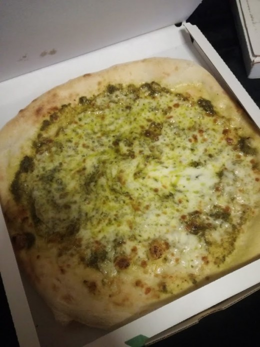 An Italian pizza topped with basil pesto sauce and stracchino cheese