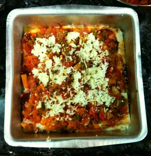 Top the bread layer with veggies, grated cheese and oregano.