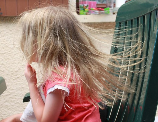 Static electricity is making this child's hair cling to the plastic chair back.