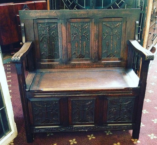 A settle - A carved wooden bench with under-the-seat storage. This was a very popular item of furniture in the 1800s.
