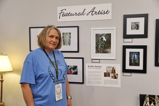 Heather Reichel in front of her photography at Meadville Fine Arts.