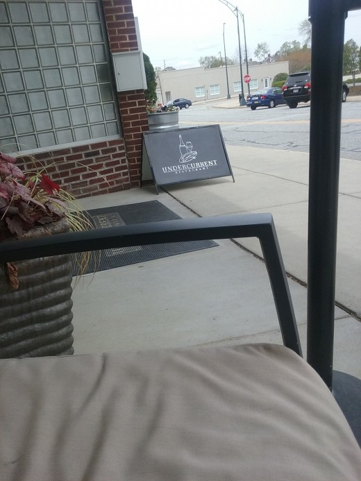 comfortable patio furniture to sit on, in front of Undercurrent Restaurant