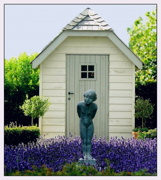 A simple garden shed in the center of a flowering garden graced with a statute.