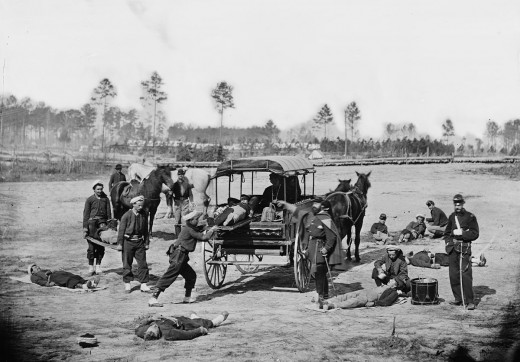 American Zouave ambulance crew demonstrating removal of wounded soldiers from the field with horses and a wagon during the American Civil War. between 1862 and 1865