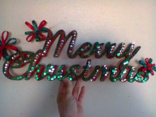 Red and green sequence and ribbon Christmas sign.