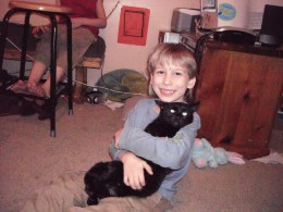 My Little Brother grasping onto our cat Nora. :)