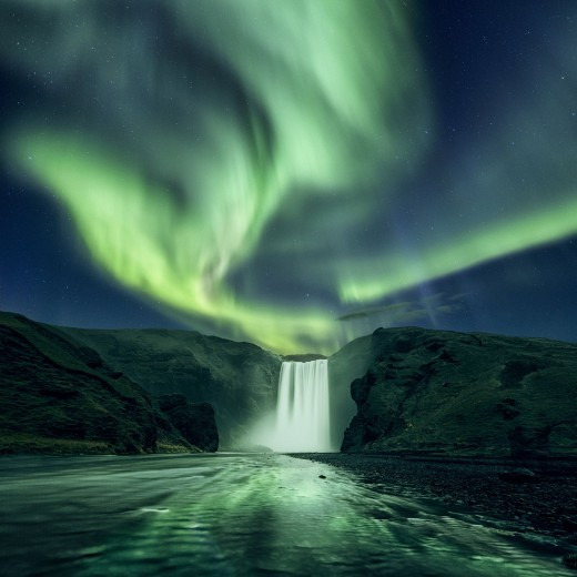 Skogafoss during winter with the spectacular Northern Lights at the background