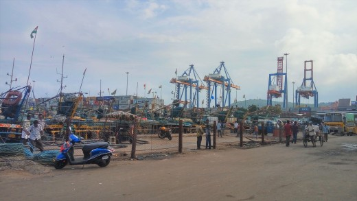 The harbor area where fishing boats are docked. Cargo containers which are stacked in the seaport area can be seen in the background.