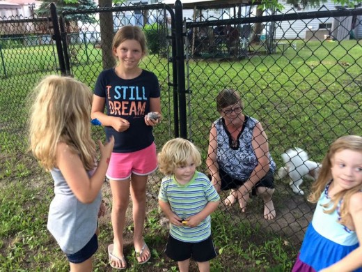 Kids meeting a local neighbor who has a cache hidden at fence.