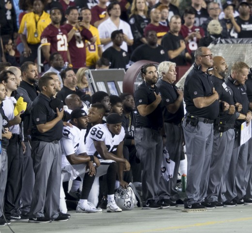 Members of the Oakland Raiders kneeling during the National Anthem.