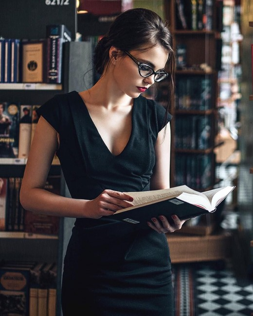 A demure librarian quietly reviews a book