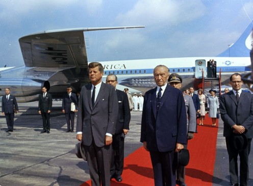 President John F. Kennedy Arrives at Wahn Airport in Bonn, Germany. President John F. Kennedy stands with Chancellor of West Germany, Konrad Adenauer (holding hat), during his arrival ceremony at Wahn Airport in Bonn, West Germany (Federal Republic)
