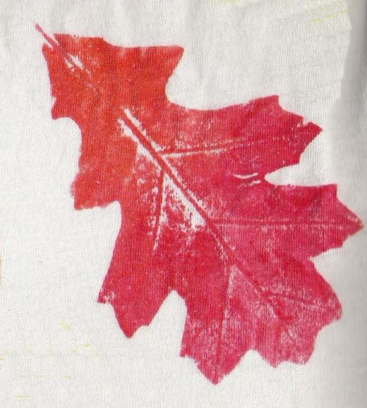 An oak leaf print on cloth using fabric paint.