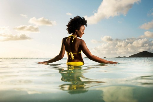 Young woman feeling the water in Antigua.   Photo Credit: Gray John Norman