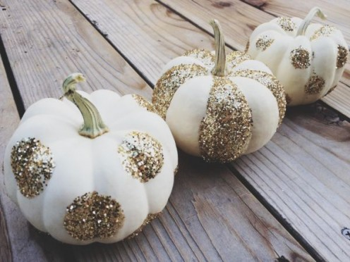 Simple craft glitter transforms little pumpkins into stylish place card holders.