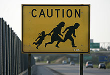 This infamous road sign warns US motorists to watch out for Mexican illegal families fleeing across I-5 Credit to Earnie Grafton, Union Trb.