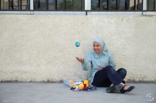 A girl excitedly plays with the ball she received in her shoebox.
