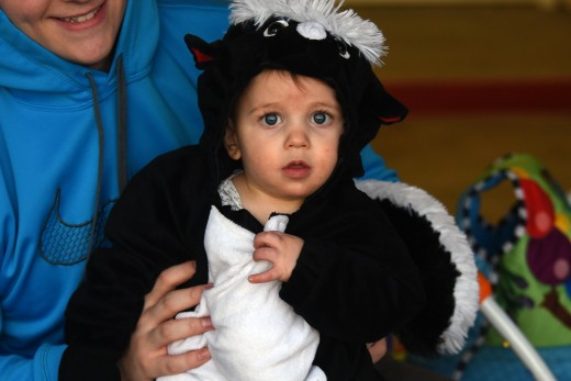 A child wearing a skunk costume