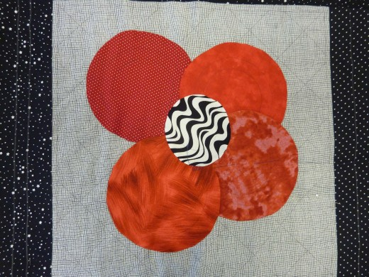 This is a simple flower applique. Red-orange petaled flower with a black and white center.
