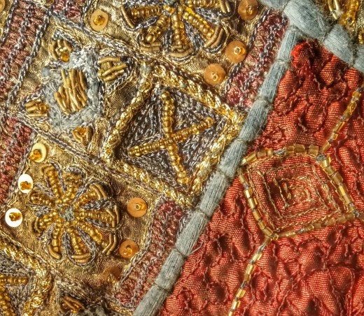 This is a sample of textile beading. Sequins and beads are stitched outlining the design patterns of the fabric.