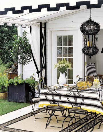 A black-trimmed awning, Greek key-patterned rugs, and elaborate lantern turn an outdoor patio into a chic dining spot. From: http://www.countryliving.com/homes/decorating-with-black-0209
