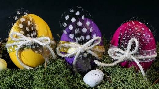 Three eggs decorated with a string of yarn and colorful feathers.