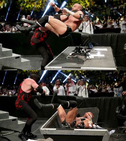 The Cerebral Assassin driven through the announcers' table by KANE during the match.