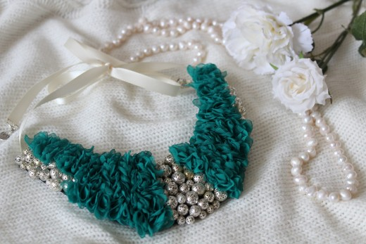 A crescent shaped bone decorated with turquoise mini-flowers and silver beads with a ribbon tie back.