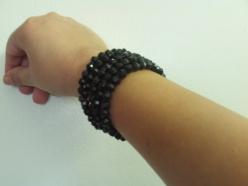 Five faux obsidian bracelets all put together, which creates the illusion of a more intricate bracelet.