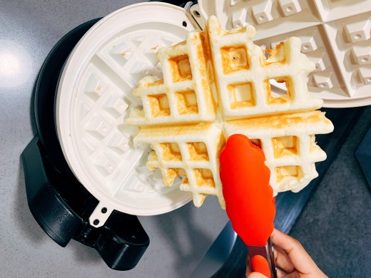Use the tongs to pick up the waffle.