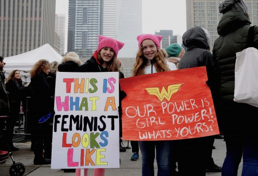 Two young girls holding signs at the 2017 Women's March in Toronto, Canada.