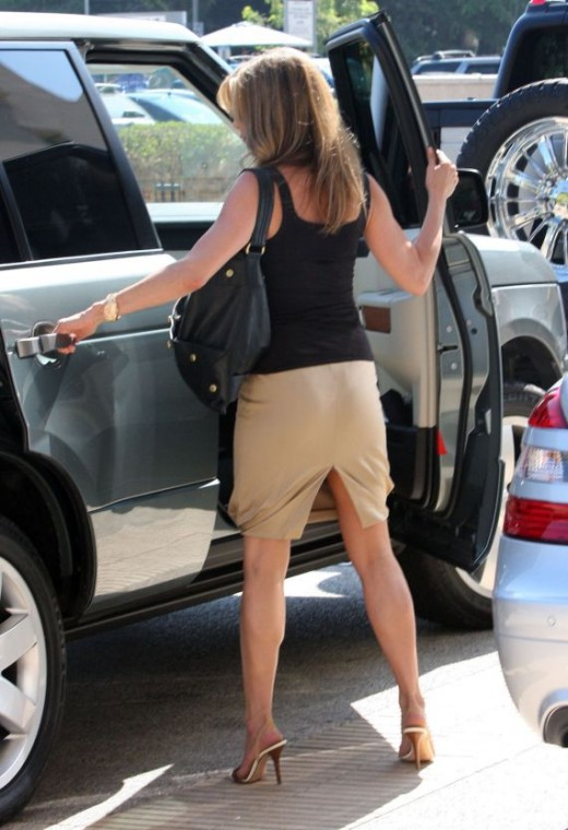 The back of Jennifer Aniston in a pencil skirt and mule high heels. Note slit up the rear of skirt
