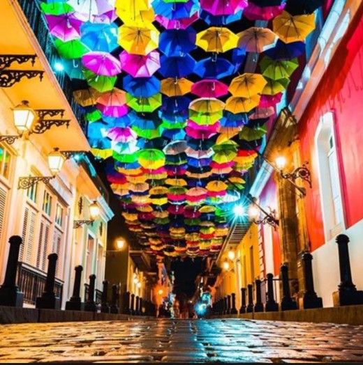 Cobblestone streets with lit up umbrellas