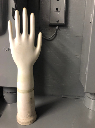 Although the background shown is one that isn't aesthetically pleasing, the glove mold is clearly shown , in it's element , industrial type background. the focus then becomes on the glove mold as it contrasts with the grey background.