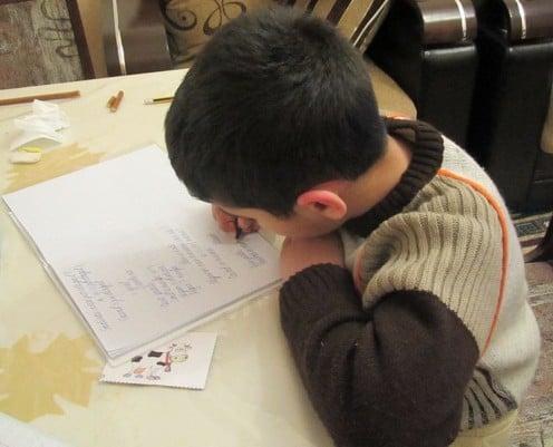 This school-boy is  reading his homework.