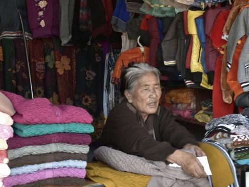 A Tibetan lady selling sweaters at Tibetan Market