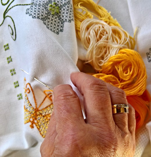 Hands at work embroidering a butterfly pattern onto fabric.