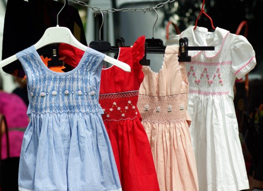 Children's smocked dresses with embroidered designs.