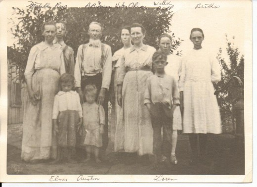 Abraham stands in the center (back row). He's wearing suspenders and has his hands touching the shoulder of one of his grandsons (Austin McGhee).