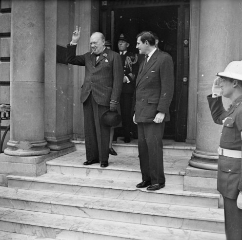 The Prime Minister Winston Churchill gives a victory salute as he leaves the American Embassy in London with John G Winant, the American Ambassador to London, on 9 May 1945