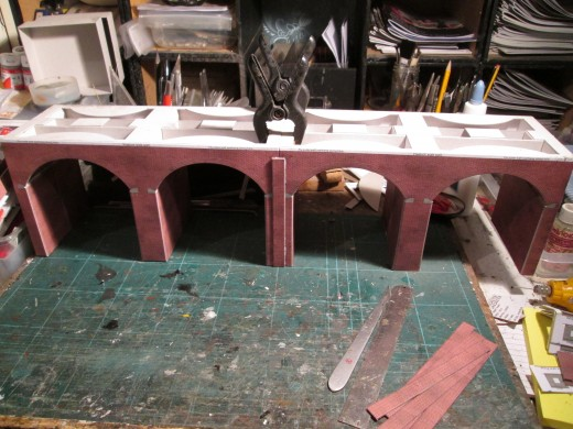 Becoming this intermediate stage before the side walls have been added. Buttresses have been added on both sides of the piers. Clamps still in place whilst the pva glue dries