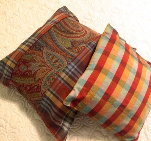 Two richly colored pillows created with expensive upholstery silks manufactured in exotic places from around the world.