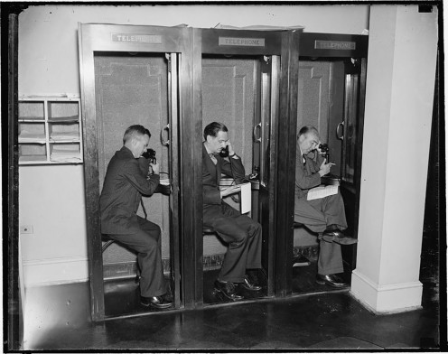 Reporters use telephones located in the White House Press Room to call the day's stories into their news desks, c. 1937.