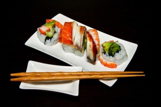 A colorful Sushi arrangement on a white platter and chopsticks. Taste exotic foods.