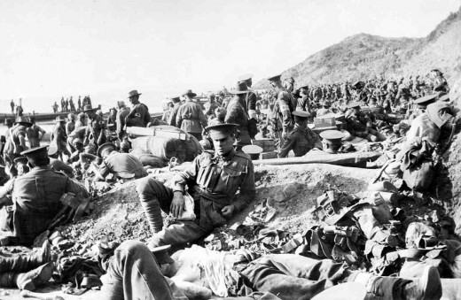 An Australian soldier lies wounded in the foreground, as hundreds of other soldiers move among the dead and wounded on the beach at Anzac Cove on the day of the landing. The soldiers wearing Red Cross armbands are tending to the wounded. Boxes of equ